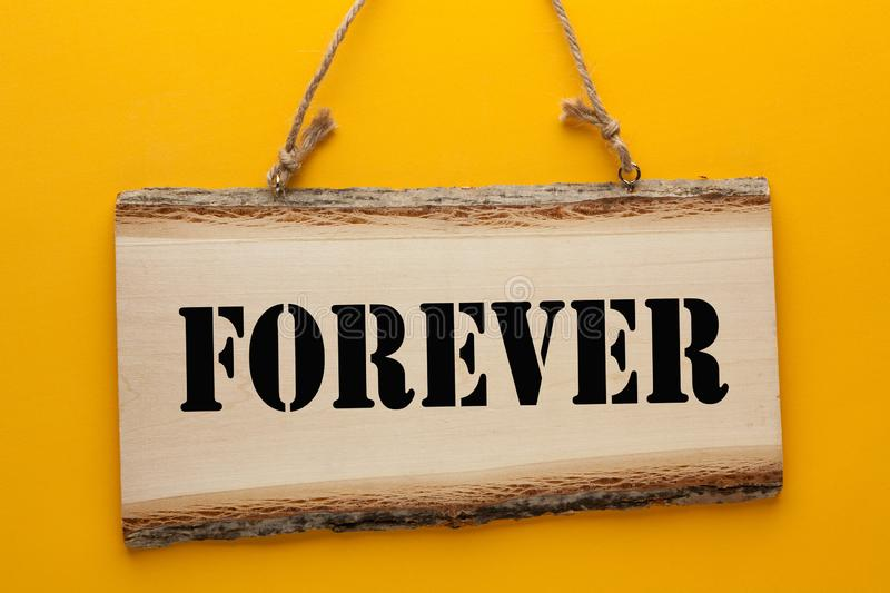 Forever On Wooden Sign. Forever word on wooden sign hanging on a rope on yellow background stock image