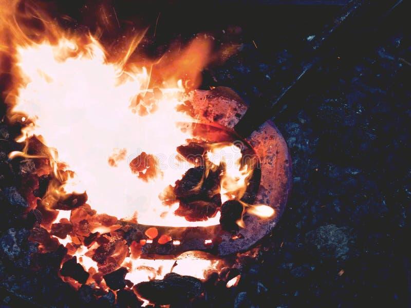 Forge avec les flammes fortes Les pinces tiennent la chaussure de cheval images libres de droits