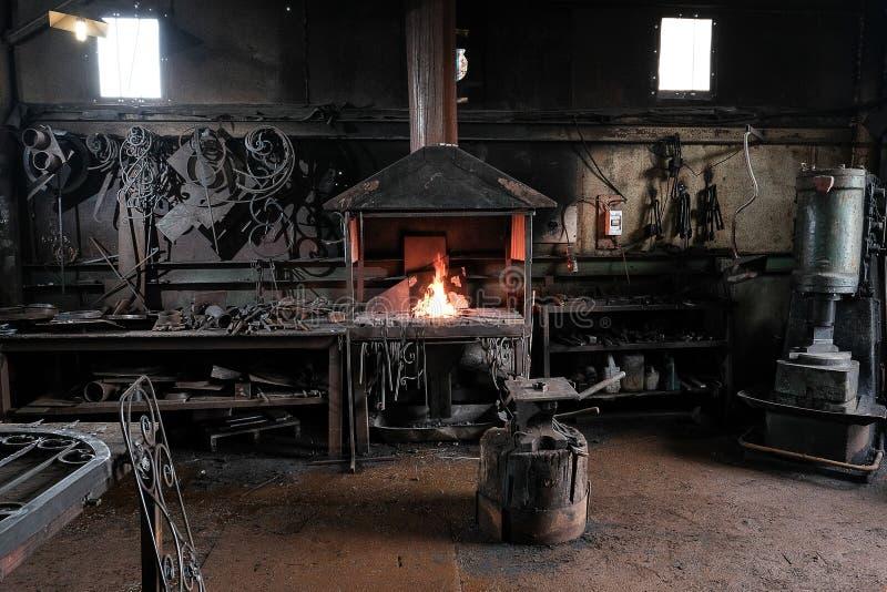 Forge, travail du ` s de forgeron, à fonte photo stock