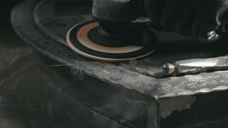Forge workshop. Smithy manual production. Polish metal with an angle grinder with an abrasive nozzle. Polishing iron. Blacksmith makes iron product for stock image