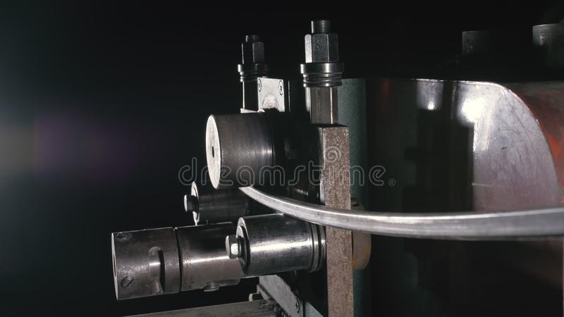 Forge workshop on table. Worker bends the metal rod on the wrought iron round bending machine. Manufacturing of a. Forge workshop on table. Smithy manual royalty free stock photo