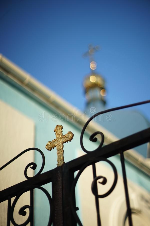 Forged black fence with a golden cross on the background of the Orthodox Church royalty free stock photography