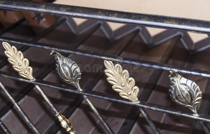 Forged elements of the stairs in the form of gold and bronze sheets stock images