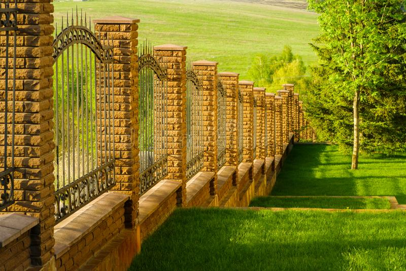 Forged fence made of metal with stone pillars royalty free stock images