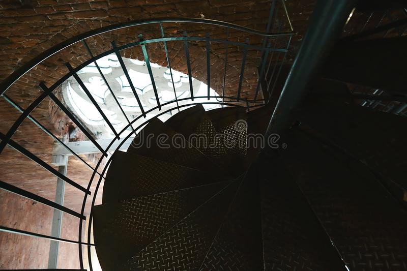 Forged iron twisted stairs with reflection on a red brick wall, handrails of the old vintage building, window with ornament royalty free stock image