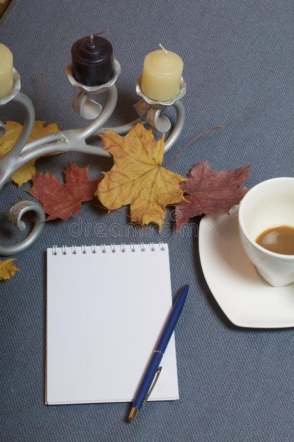 Forged metal candlestick with candles. A cup with unapproved coffee. There is an open notepad and a pen. Fallen autumn leaves of y stock photos
