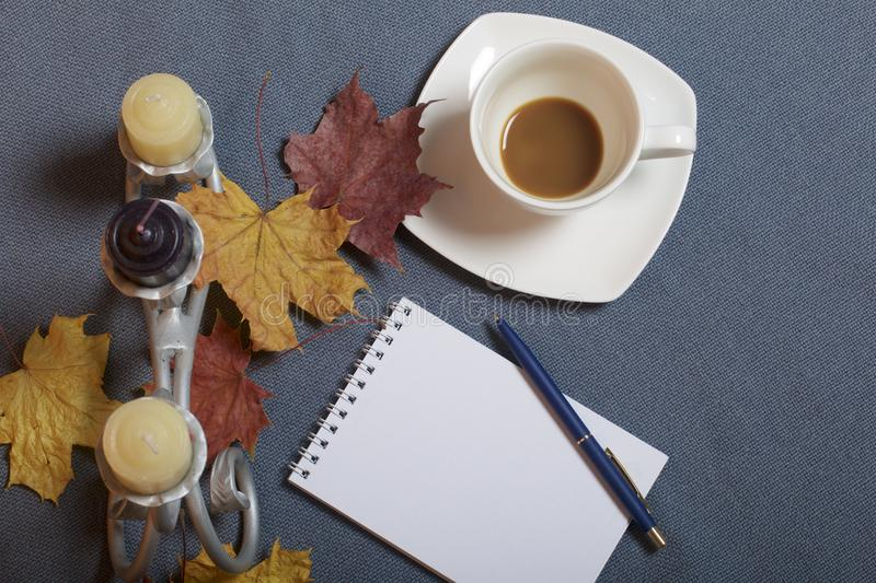 Forged metal candlestick with candles. A cup with unapproved coffee. There is an open notepad and a pen. Fallen autumn leaves of y stock images