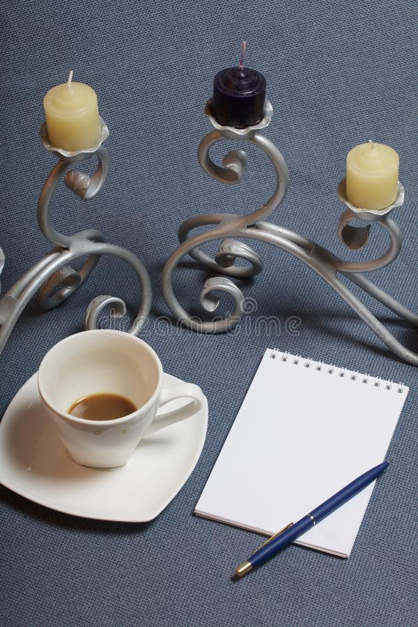 Forged metal candlestick with candles. A cup with unapproved coffee. There is an open notepad and a pen. Fallen autumn leaves of y stock photo