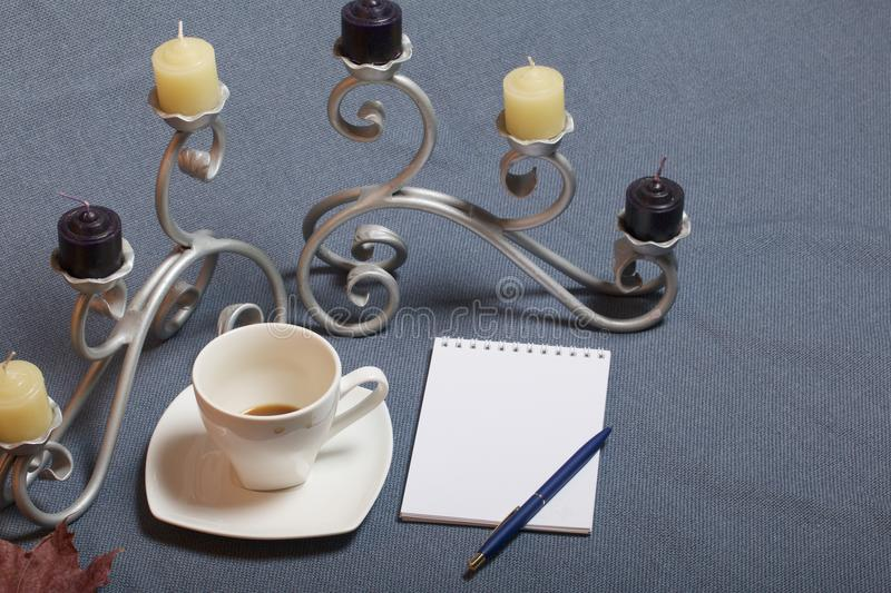 Forged metal candlestick with candles. A cup with unapproved coffee. There is an open notepad and a pen. Fallen autumn leaves of y royalty free stock photography