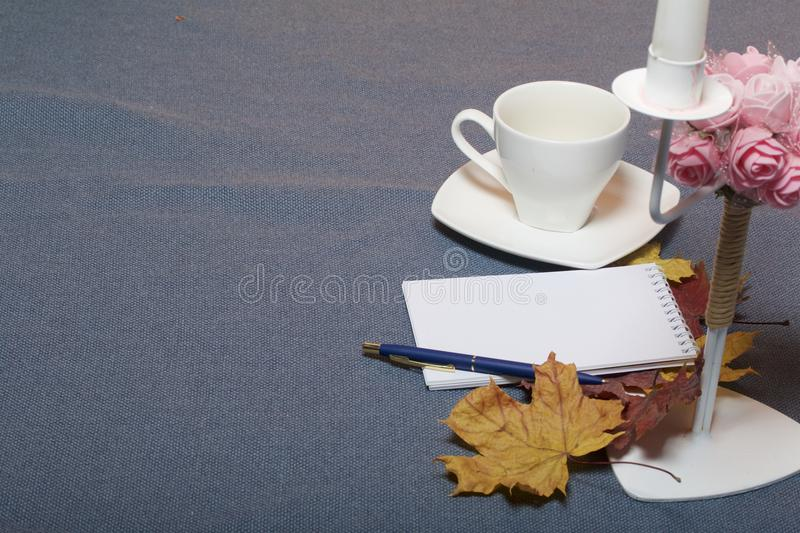 Forged metal candlestick with candles. There is an open notepad and a pen. A cup with unapproved coffee. Fallen autumn leaves of y stock images
