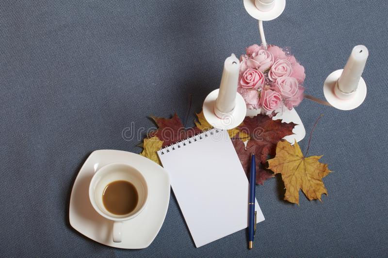 Forged metal candlestick with candles. There is an open notepad and a pen. A cup with unapproved coffee. Fallen autumn leaves of y royalty free stock images