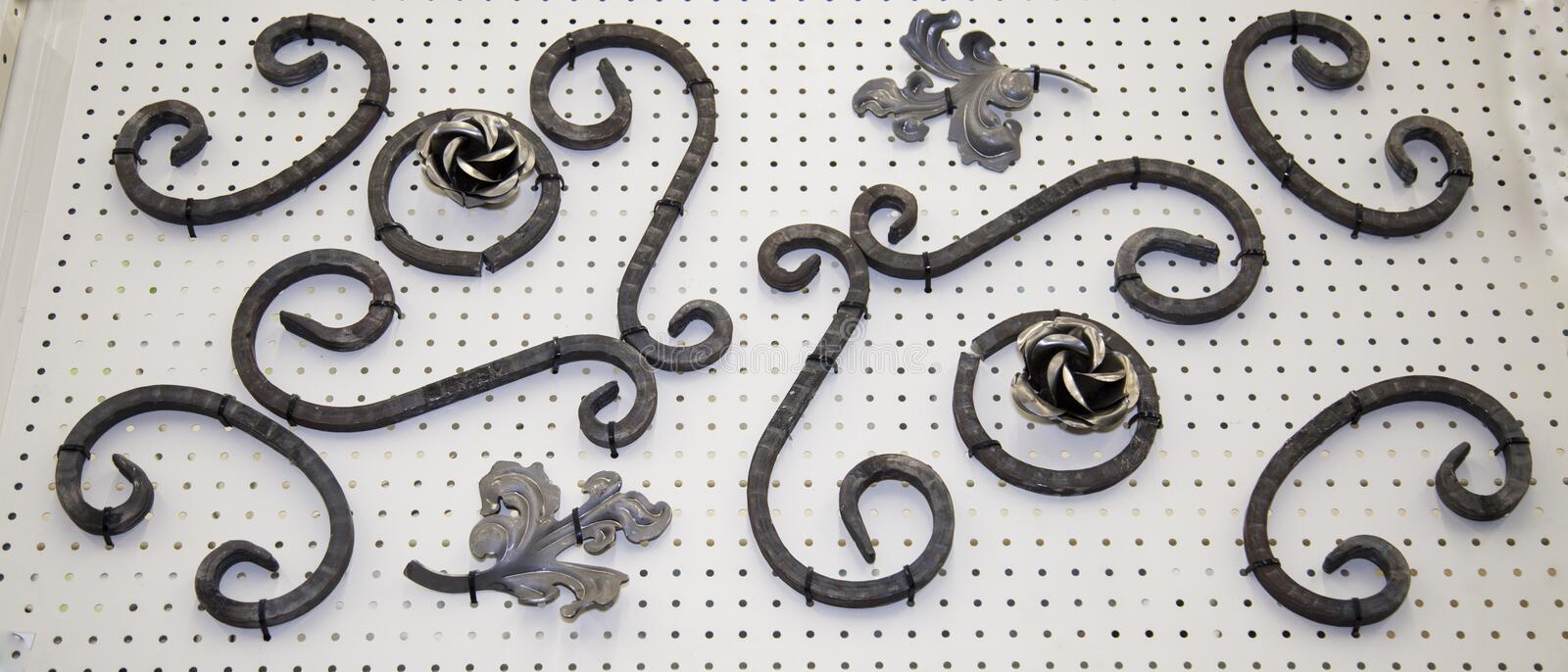 Forged metal products in the form of curls, circles, flowers, leaves fixed on a white stand. Construction, repair, art stock photography