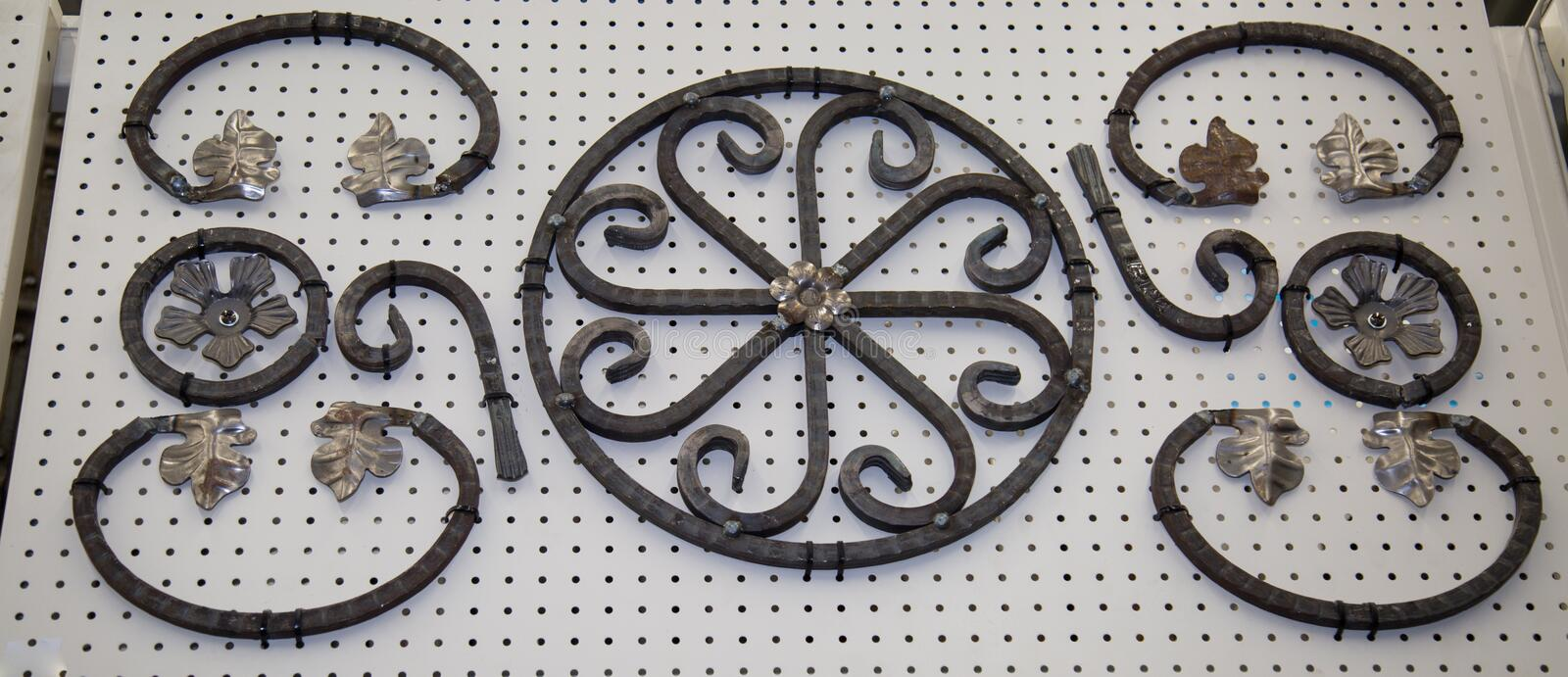 Forged metal products in the form of curls, circles, flowers, leaves fixed on a white stand. Construction, repair, art. Design royalty free stock photography