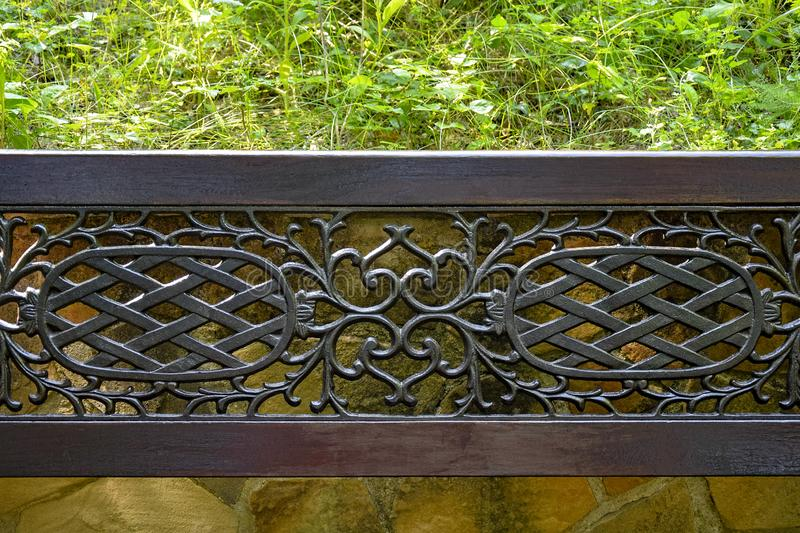 Forged openwork lattice in a wooden frame on the background of a wall of wild stone and green vegetation. A fragment of a street. Bench located in a cozy park royalty free stock photography