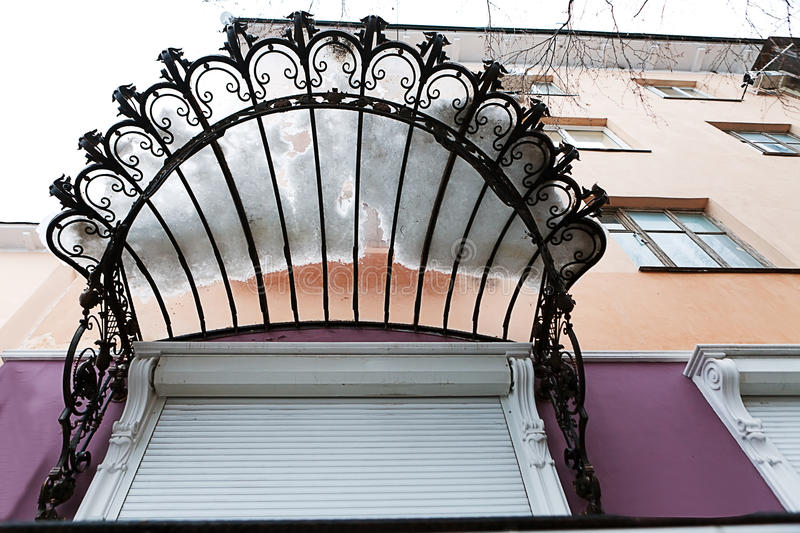 Forged openwork visor of front door of house. Looks from the bottom stock images