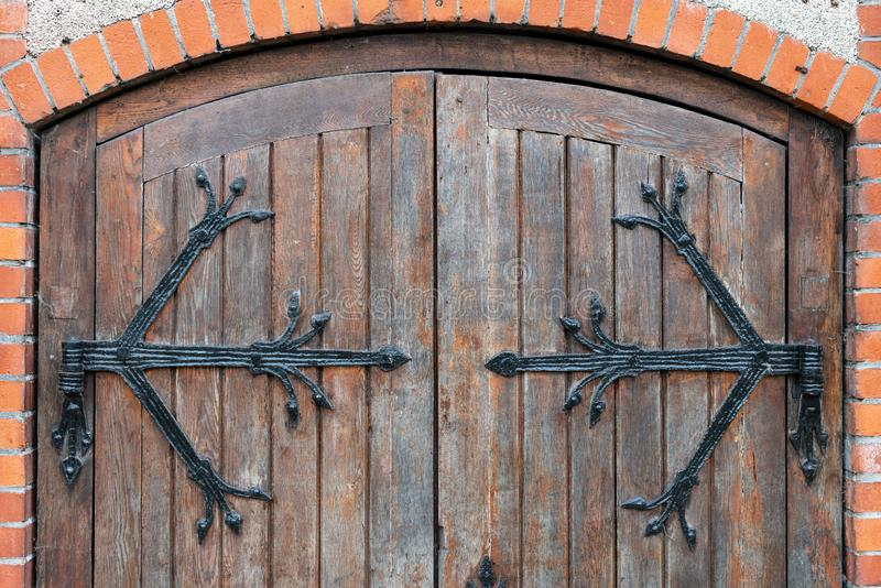 Forged pattern on door with decorative elements, Old vintage entrance, massive heavy wooden door of church or cathedral. Forged pattern on door with decorative stock photo