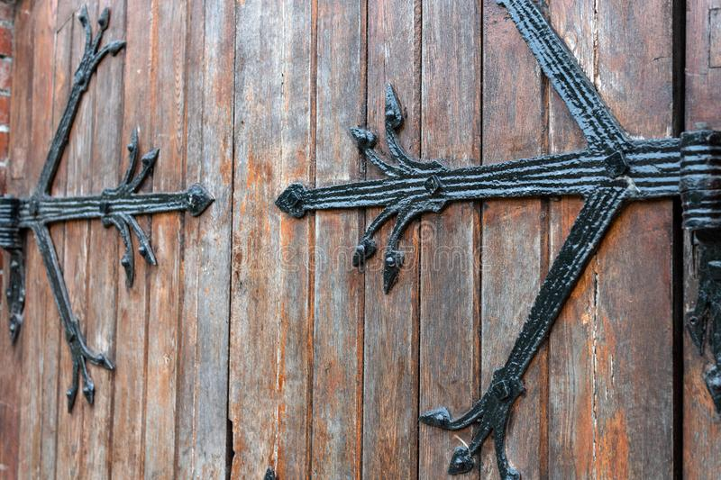 Forged pattern on door with decorative elements, Old vintage entrance, massive heavy wooden door of church or cathedral. Forged pattern on door with decorative royalty free stock image