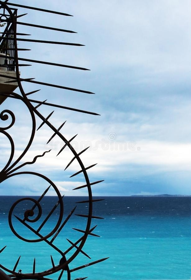 Forged spiral metal stylish architectural design detail element on blue sky and sea water background stock photo