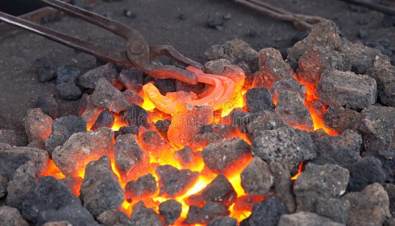 Forgeron d'artisan chauffant un fer à cheval dans le feu photos stock