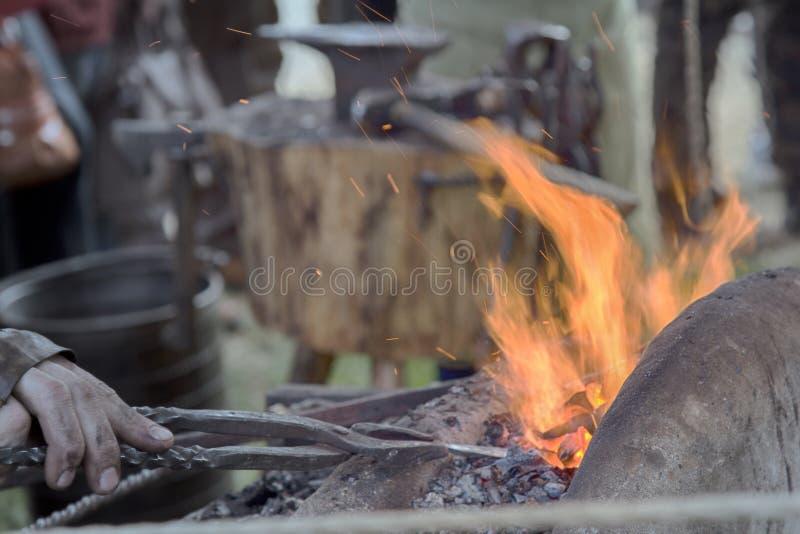 Forgeron de village près des soufflets et enclume au travail image stock