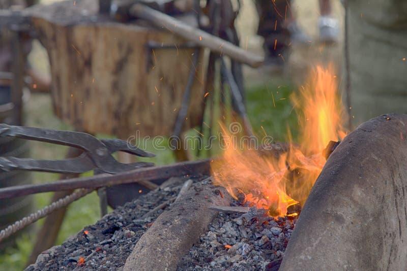 Forgeron de village près des soufflets et enclume au travail photo stock