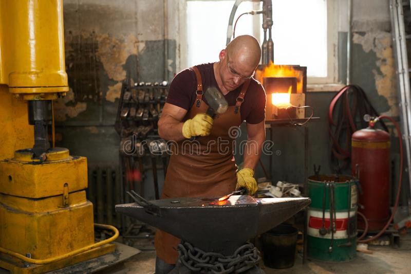 Forgeron frappant la barre en métal avec le marteau images stock