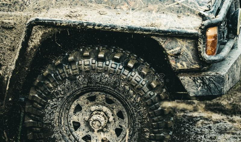 Forget about driving on smooth tarmac. Car racing offroad. Offroad car in action. Dirty car drive on high speed. SUV or. Offroader on mud road. Car wheels on stock photography