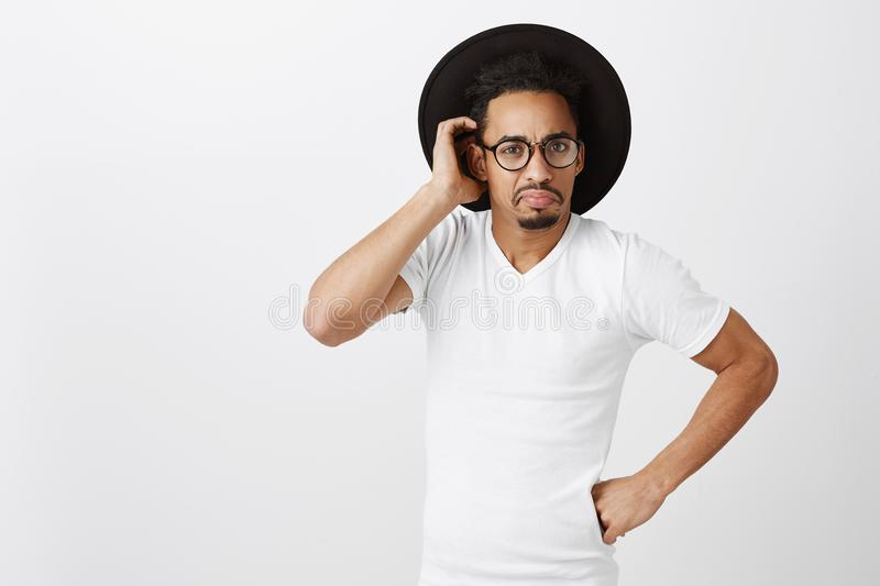 Forgetful guy lost wallet. Portrait of confused curious dark-skinned boyfriend in trendy glasses and hat, holding fist stock photos