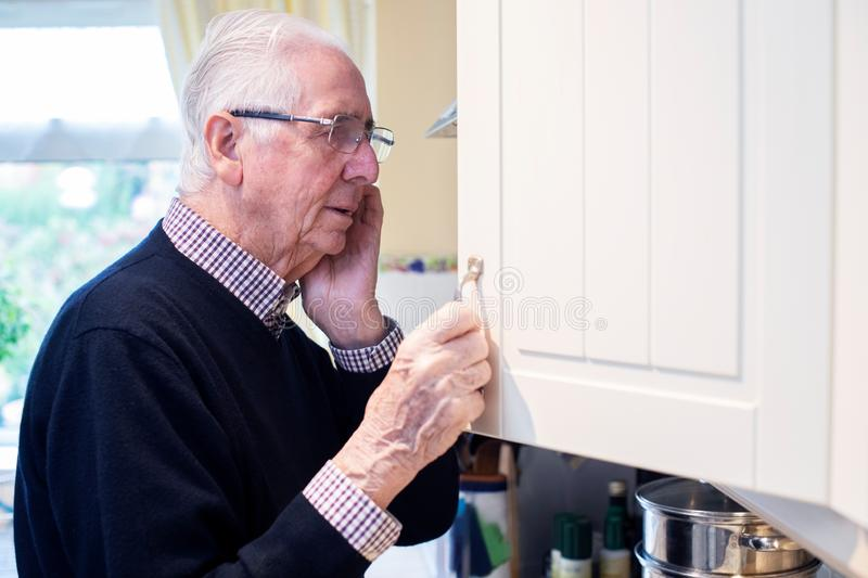 Forgetful Senior Man With Dementia Looking In Cupboard At Home. Forgetful Senior Man With Dementia Looks In Cupboard At Home stock photo
