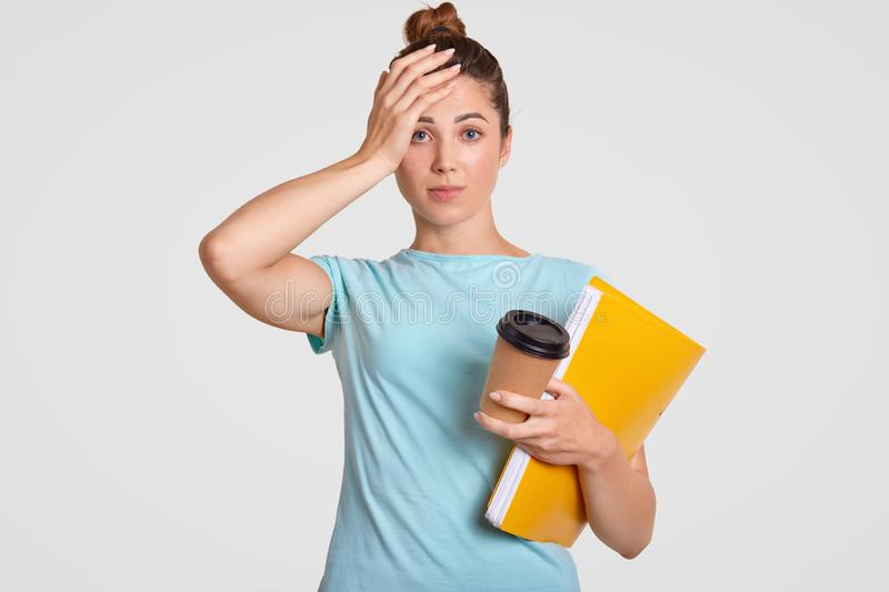 Forgetful stressful college student keeps hand on head, dressed in casual clothes, has bad memory, headache after long work, has d royalty free stock image