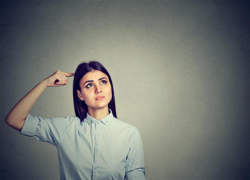 Forgetful young woman scratching head royalty free stock photo