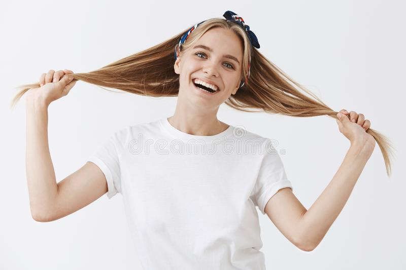 Forgetting that I am adult. Playful happy and childish attractive fair-hair female in headband, smiling broadly, holding royalty free stock images