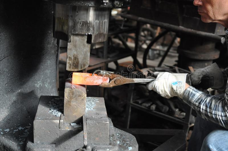 Forging red hot steel in pneumatic forge hammer. Forging red hot steel hammer head in traditional air hammer or pneumatic hammer stock images
