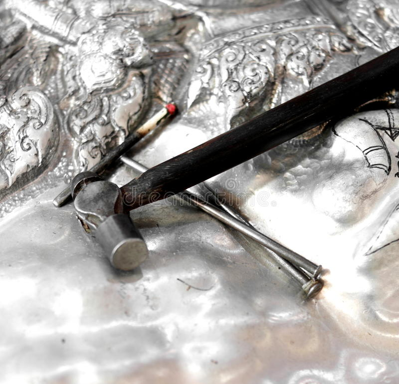 Forging the Silver. Detail of tools on a sheet of silver stock photo