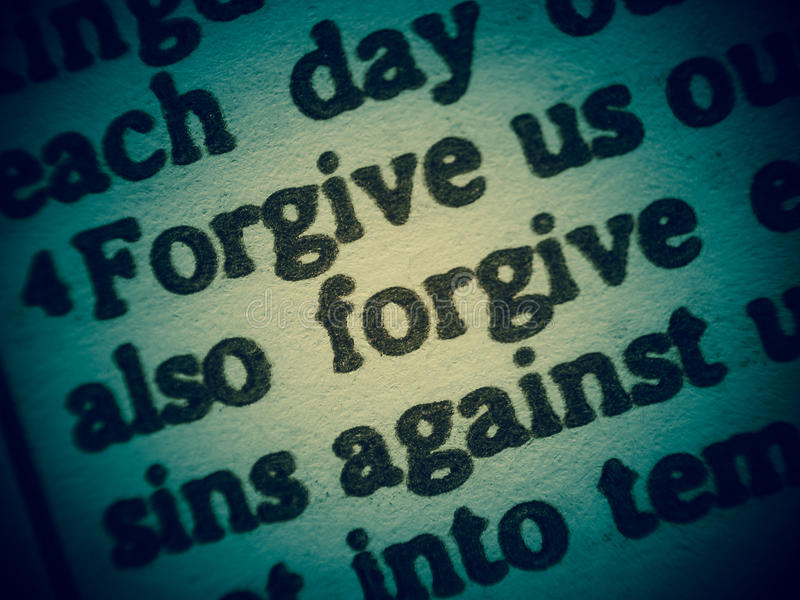 Forgive us our sins(Lord´s Prayer). Low Depth of Field macro shot of a Bible text from the Gospel of Luke chapter 11 verse 4 with the words of Jesus called stock image
