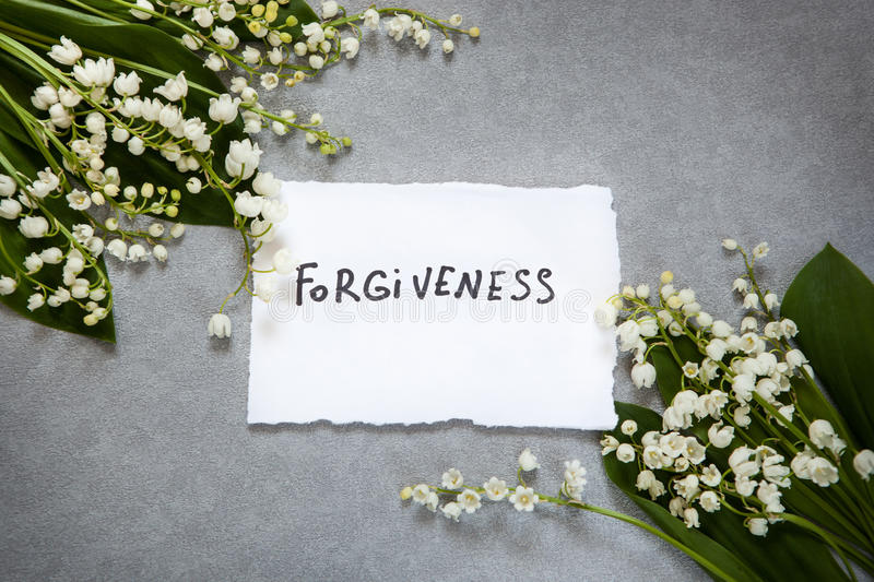 Forgiveness word with white flowers. Forgiveness word on gray background with white flowers royalty free stock photography