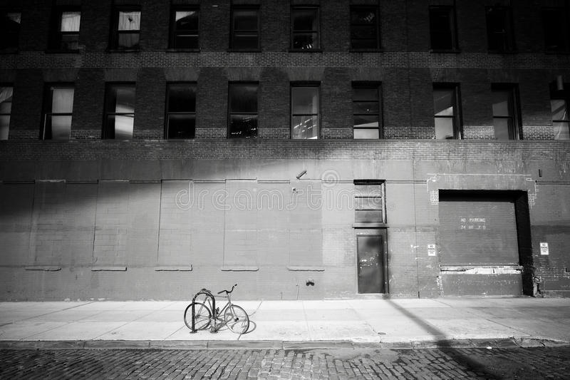 Forgotten bike. Bicycle locked by a street in Dumbo neighborhood. At sunset, New York City, USA royalty free stock photo