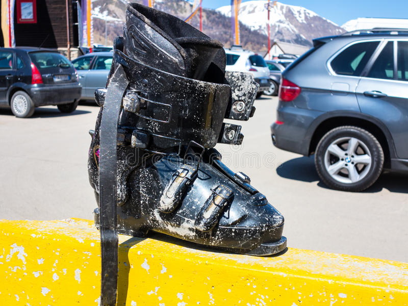 Forgotten dirty mountain ski boot on the parking royalty free stock photo