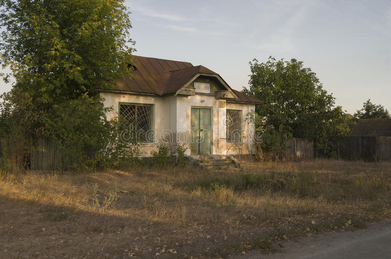 Forgotten old building in little suburb. Early fall trees of green and tint of yellow colors stock photography