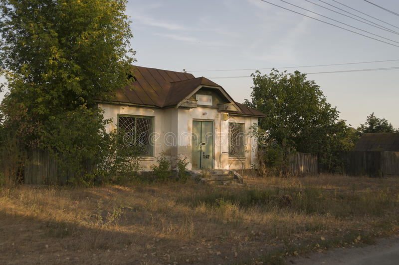 Forgotten old building in little suburb. Early fall trees of green and tint of yellow colors stock photo