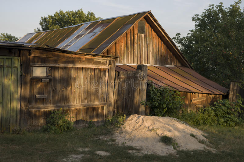 Forgotten old building in little suburb. Early fall trees of green and tint of yellow colors royalty free stock images