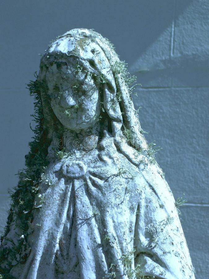 Forgotten saintly statue in repose. Solitary statue stands alone with lichen growing on it royalty free stock photos
