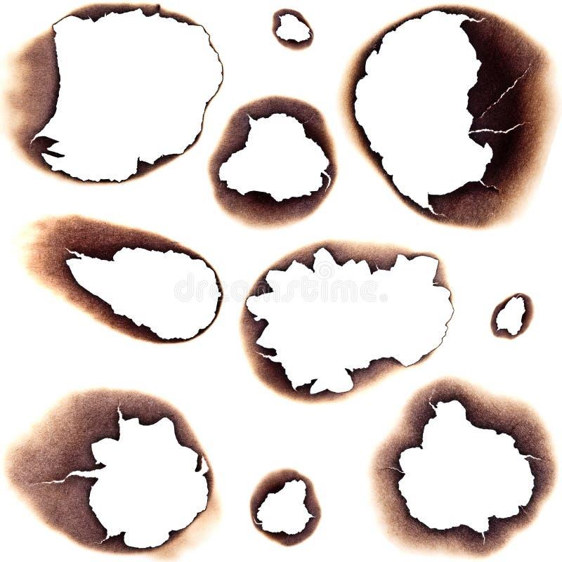 Fori bruciati in Libro Bianco fotografia stock libera da diritti