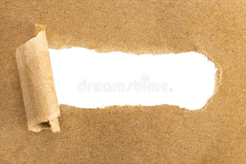 Fori in carta marrone con i lati lacerati sopra fondo di carta con fotografie stock
