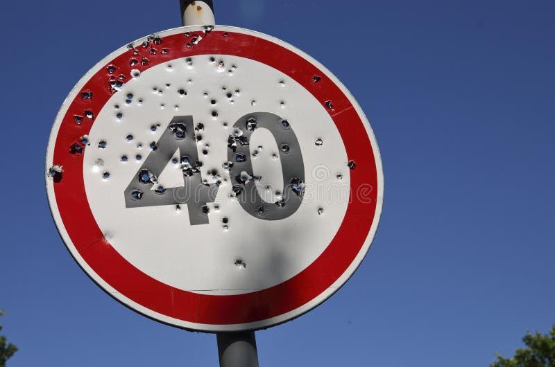 Fori di pallottola sul segnale stradale limite di velocità fotografie stock libere da diritti