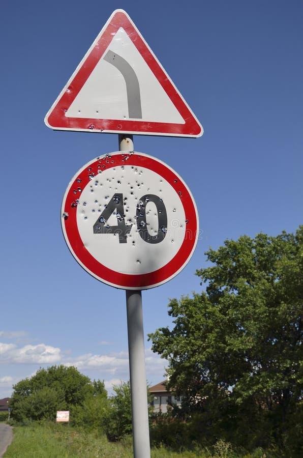 Fori di pallottola sul segnale stradale limite di velocità immagine stock libera da diritti