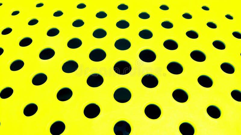 Fori rotondi neri su una superficie gialla piana andare avanti come i precedenti immagini stock libere da diritti