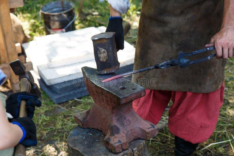forja O ferreiro processa o metal caloroso com um malho no batente Trabalho manual de um ferreiro fotografia de stock royalty free