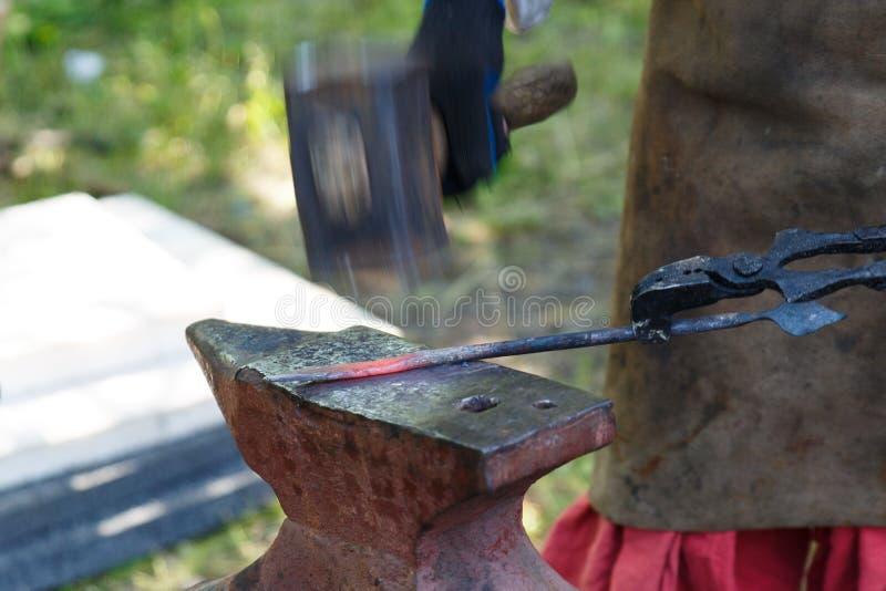 forja O ferreiro processa o metal caloroso com um malho no batente Trabalho manual de um ferreiro imagens de stock royalty free