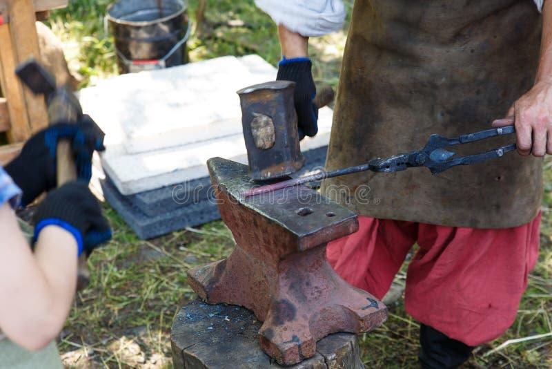 forja O ferreiro processa o metal caloroso com um malho no batente Trabalho manual de um ferreiro imagem de stock